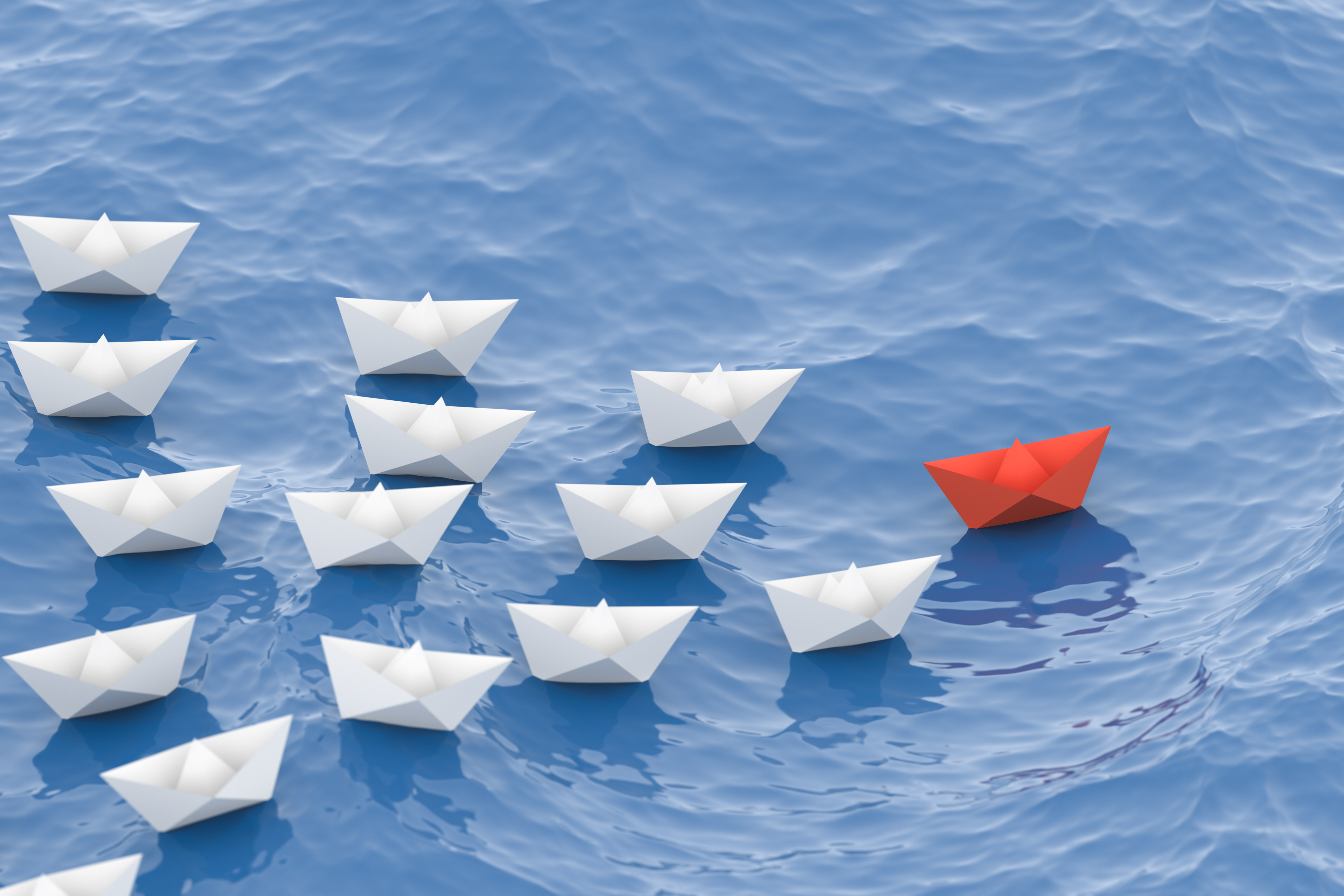 Paper boats - red one leading -white ones following - leadership resolutions for global development professionals
